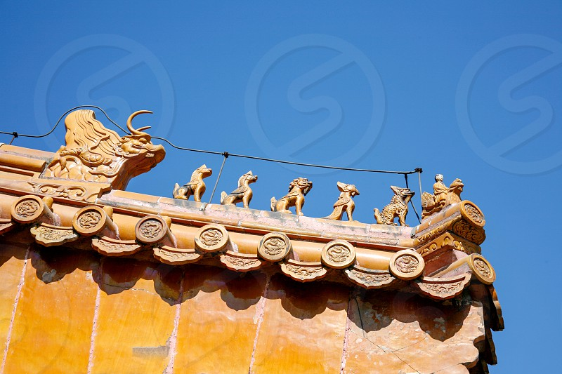 Roof of traditional chinese temple with orange ceramic tiles and an ornate red stone gable photo