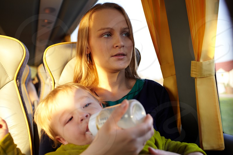 Young mother is feeding her two year old son with milk while they are travelling by intercity bus. Close up portraits. photo