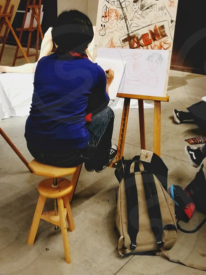 woman wearing blue shirt sitting on stool making sketch on easel with canvas photo