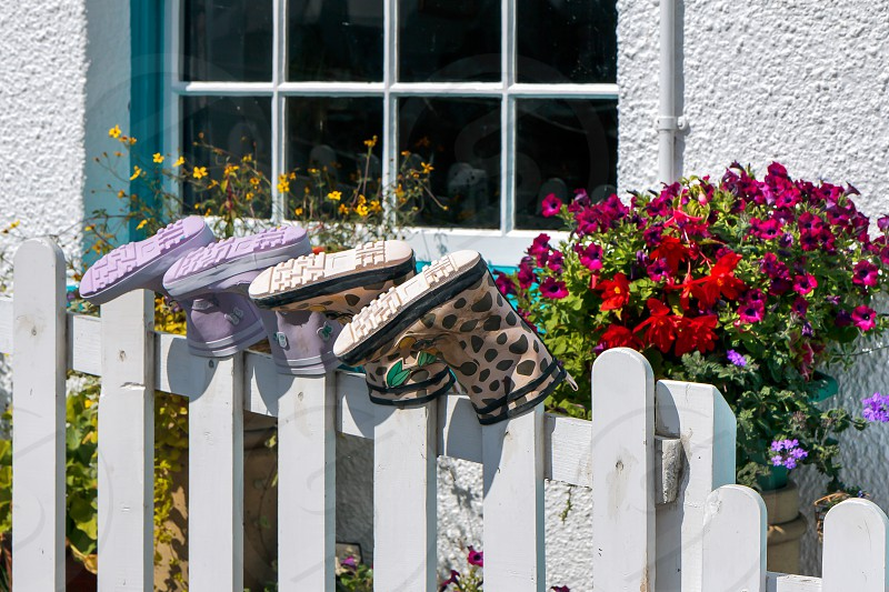 Two Pairs of Boots Placed on Fence Posts photo