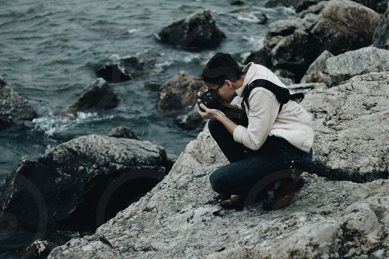 man crouching on a rock taking a photo of water photo