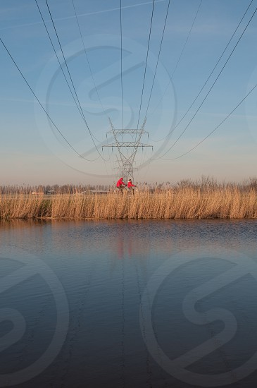 2 bicyclist passing under power lines near lake photo