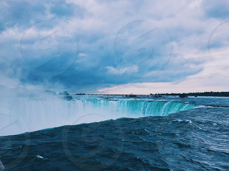 Niagara Falls modern art landscape beautiful wonderful cool water boat mist fog awesome mighty cliff waterfall Canada buffalo New York river lake blue rocks contrast nature birds hornblower maid of the mist sky clouds rushing water danger large rain clouds weather gorgeous photo