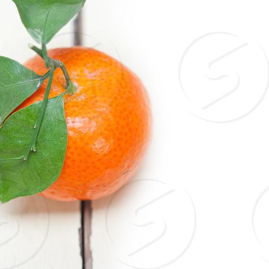 tangerine mandarin orange on white rustic wood table photo