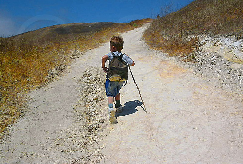 Seen from behind a small boy hikes up the hill of a desert path using a small hiking stick photo