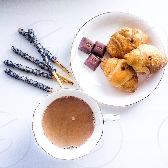 pastry and chocolate on white ceramic round plate beside beverage on white ceramic teacup photo