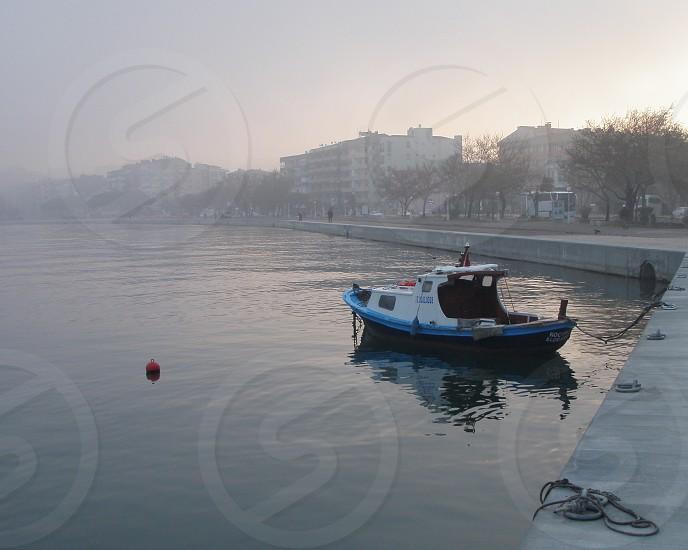 Fishing boat foggy morning in Channakale Turkey photo