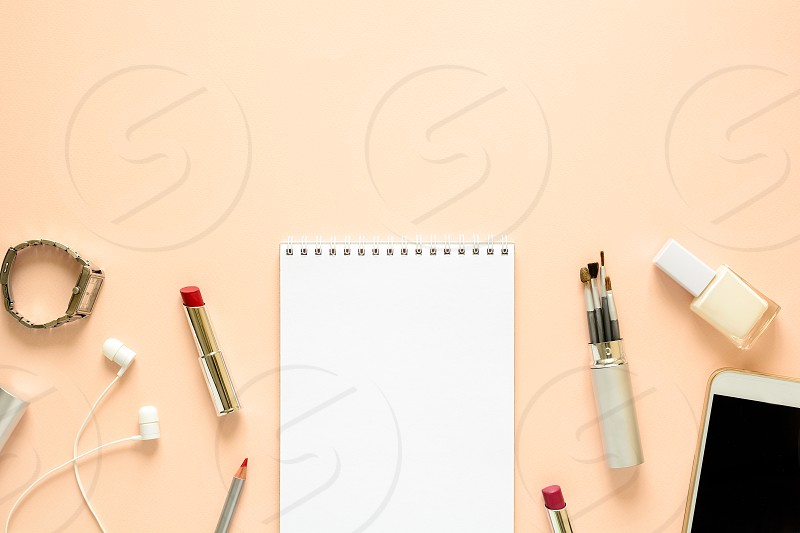 Feminine workspace with smartphone headphones notebook pencil nail polish clock brushes and lipstick. Flat lay. Top view. Copy space photo