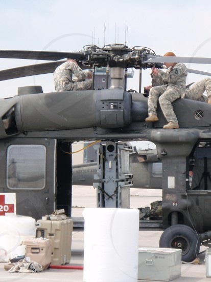 soldiers fixing the helicopter photo
