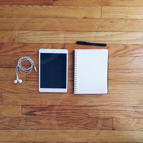 iPad mini and notebook on wood flooring photo