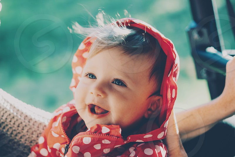 A baby girl sitting in her moms lap smiling at her as wind blows through her hair and sun is setting photo