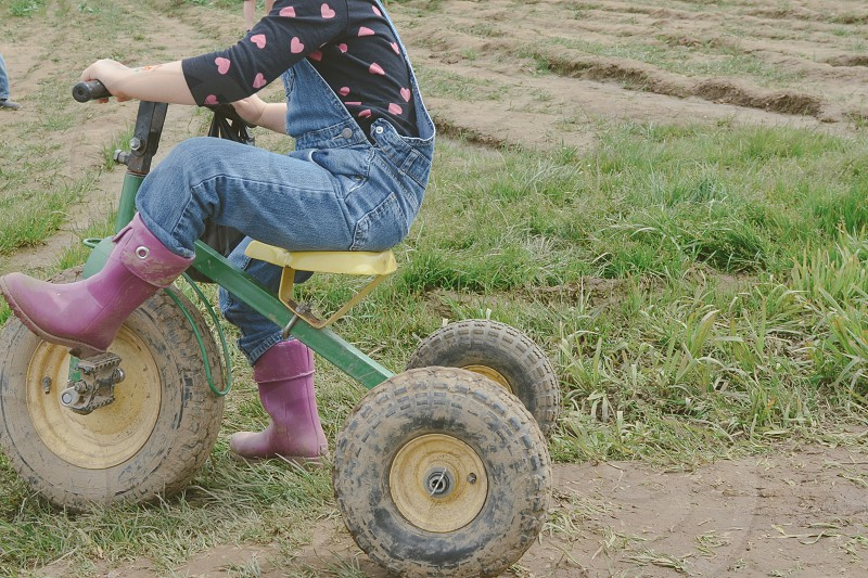 Tractor bike child purple boots country living rustic lifestyle girl overalls photo