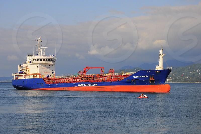 blue white and orange cargo ship on water during daytime photo