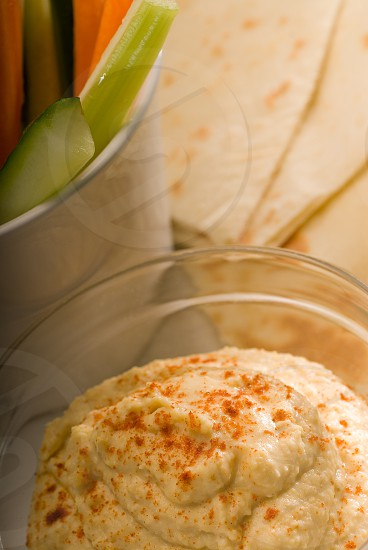 middle eastern hummus dip on a glass bowl with homemade pita bread and raw vegetable photo