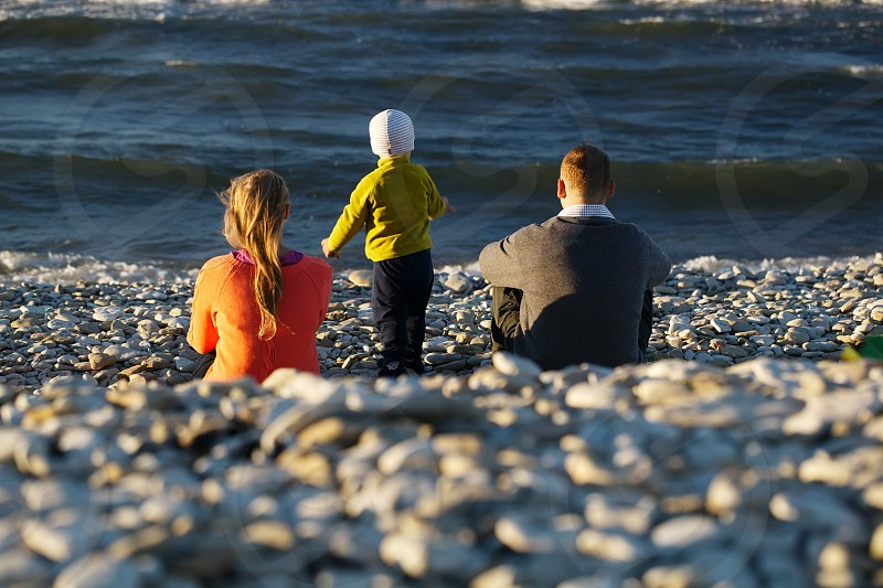 Mother father and their little son sitting on pebble beach watching moving waves photo