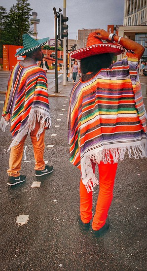 man and woman wearing multi colored poncho and mexican hats during daytime in road photo