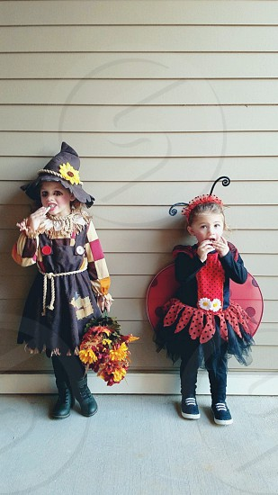 toddler girls eating candy dressed in halloween costumes photo
