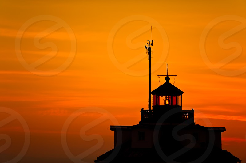 Silhouette of a lighthouse against an orange sunset. photo
