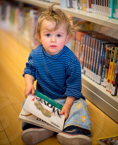 Baby boy playing with a book photo