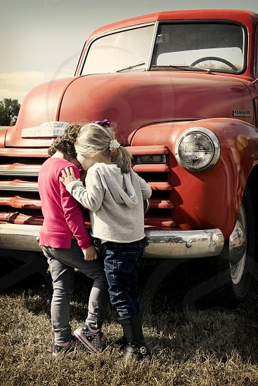 Young girls telling secrets by an old red pickup truck. Best friends. photo