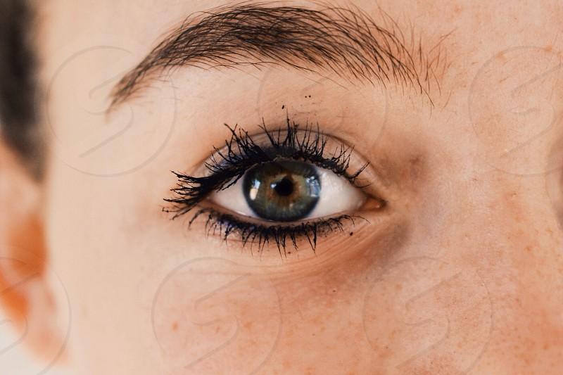 close up photo of gray right eye with black mascara photo