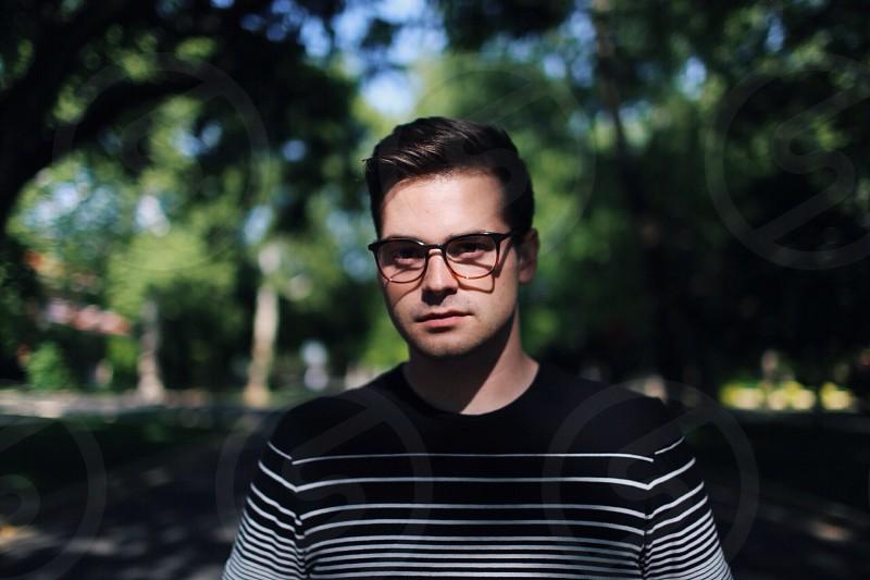 man in eye glasses brown hair striped black white sweater in park photo