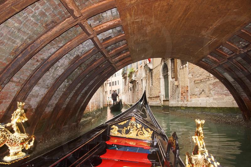 Venice Canal on a Gondola ride under a bridge photo