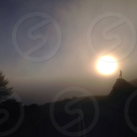 man standing on cliff under foggy sunny view photo