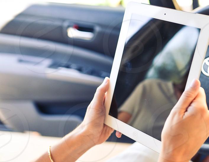 woman using white ipad in car photo