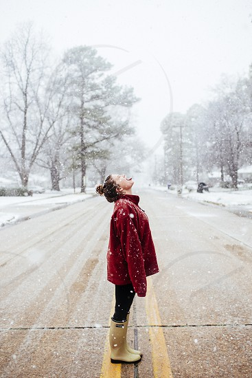 woman in red jacket standing on middle of road looking up with open mouth under falling snow photo