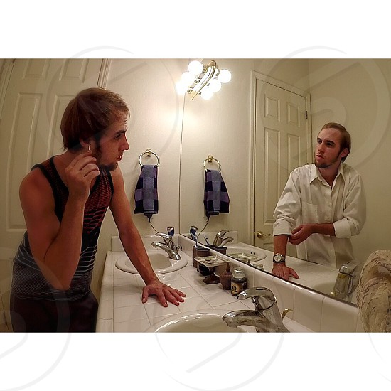 photo of man in bathroom with reflection of another man wearing different apparel on mirror photo