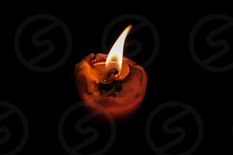 Old lit orange candle slowly dying photo