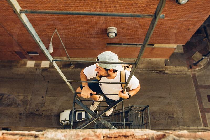 bird's eye view man wearing white crew neck t-shirt climbing up black ladder on brown concrete building during daytime photo