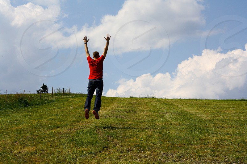 man in red t shirt jumping on green fields photo