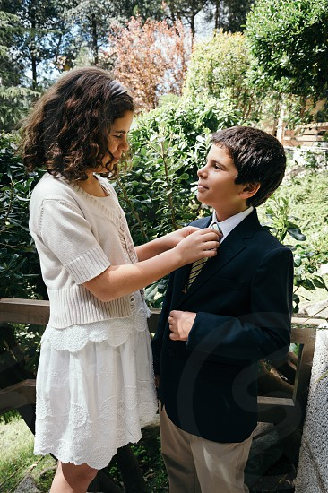 Sister knotting his tie to her brother in the garden a sunny day photo