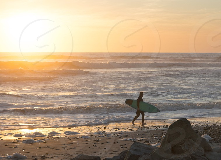 surfer walking on shore during sunset photo