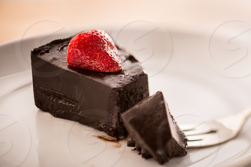 Chocolate mousse topped with a slice of strawberry on a white plate with a dessert fork. photo