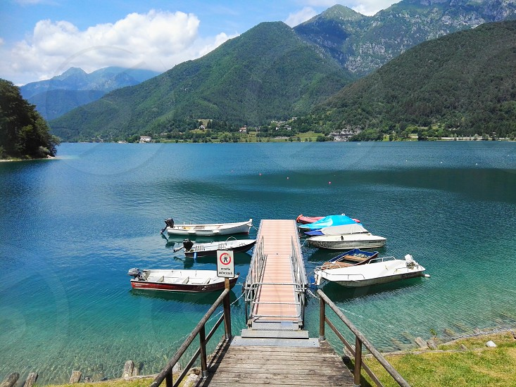 high angle photography of dock near the boats in body of water surrounded by mountains during daytime photo