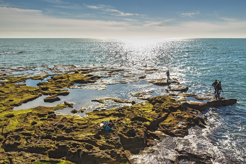 Cadiz Spain - Dec 2018: Men fishing off the rocks of Paseo Fernando Quinones photo