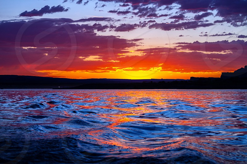 Stunning pink yellow and blue sunset reflected on the water at Wahweap Bayin the Arizona portion of Lake Powell.  The clouds seem to be on fire in the golden hour light as the waves roll with their colors below. photo