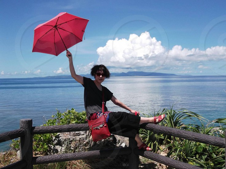 person wearing red sling bag and holding red umbrella while sitting on fence near at body of water during daytime photo