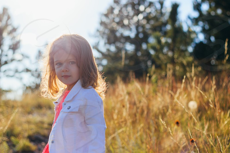 a young girl on a hike in the woods at sunset photo