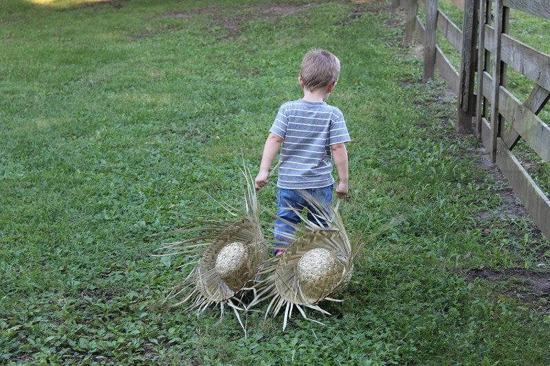 Young boy dragging straw hats photo