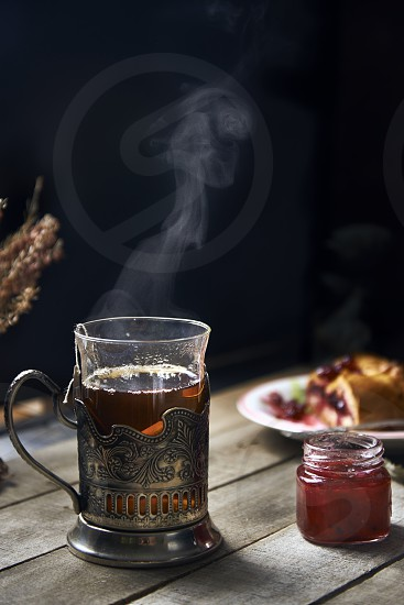 Hot tea in a traditional Russian glass holder jam and a piece of fruit pie on a wooden rustic background photo