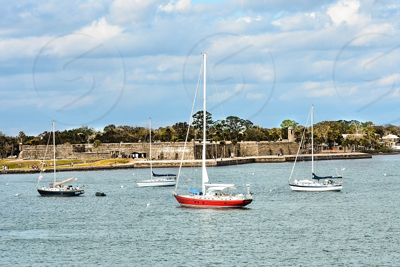 St. Augustine Florida. January 26  2019. Sailboat and Castillo de San Marcos Fort on lightblue sky background in Florida's Historic Coast. photo