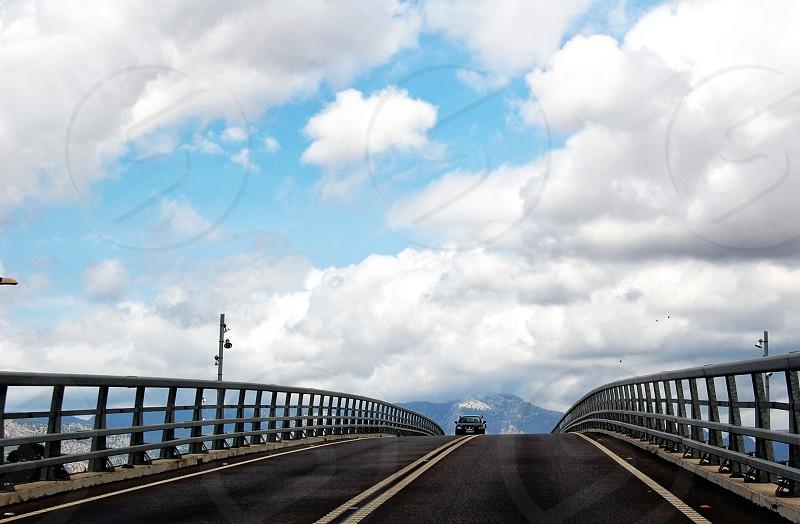 white fluffy clouds over a bridge photo