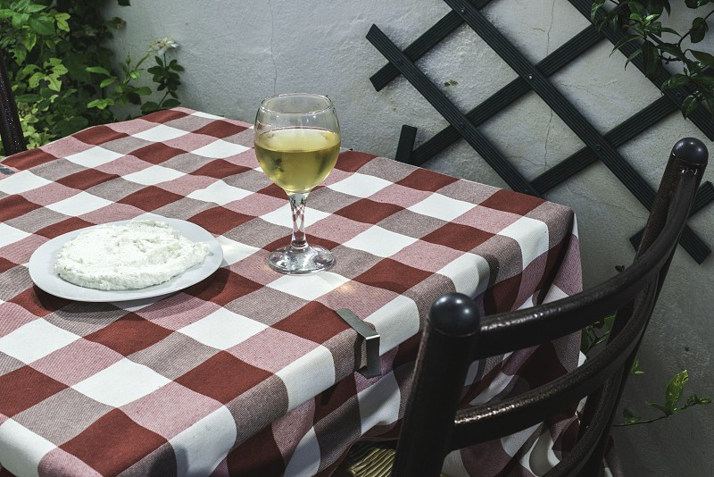 Table in restaurant in Greece. Red cover and glass of wine photo