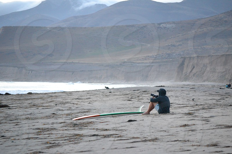 man in grey hoodie and heather grey shorts sitting on brown sandy beach shore by green and white surfboard during daytime photo
