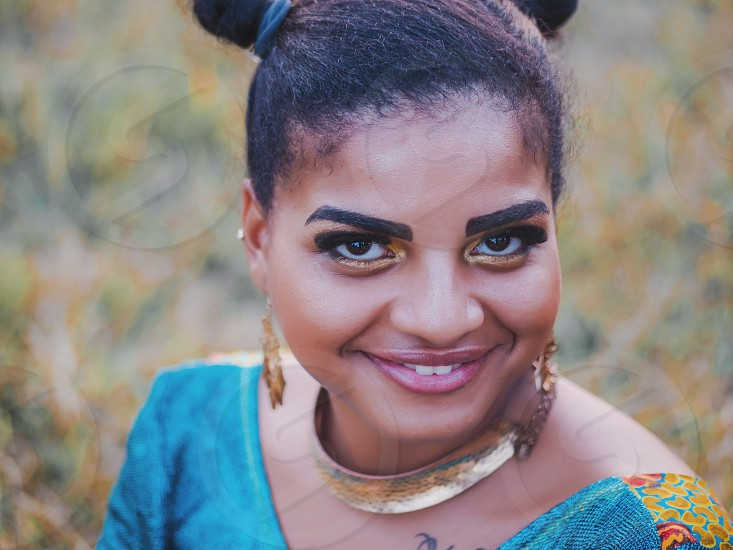 Portrait of young afro-american gypsy woman in colorful blue traditional dress and gold jewelry smiling and looking into camera. Sexy fashion girl photo