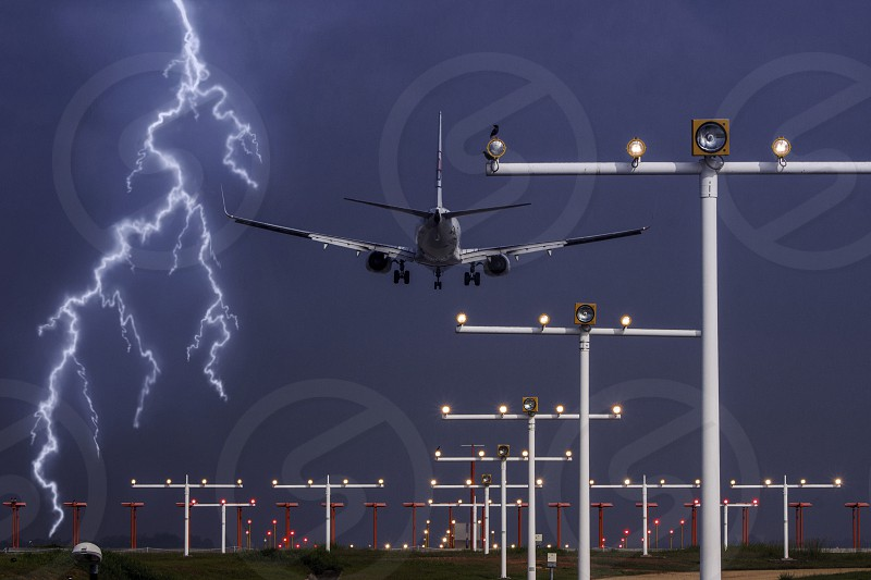 a commercial aircraft is ready to touch down on a runway in a stormy weather with lightning in the background photo
